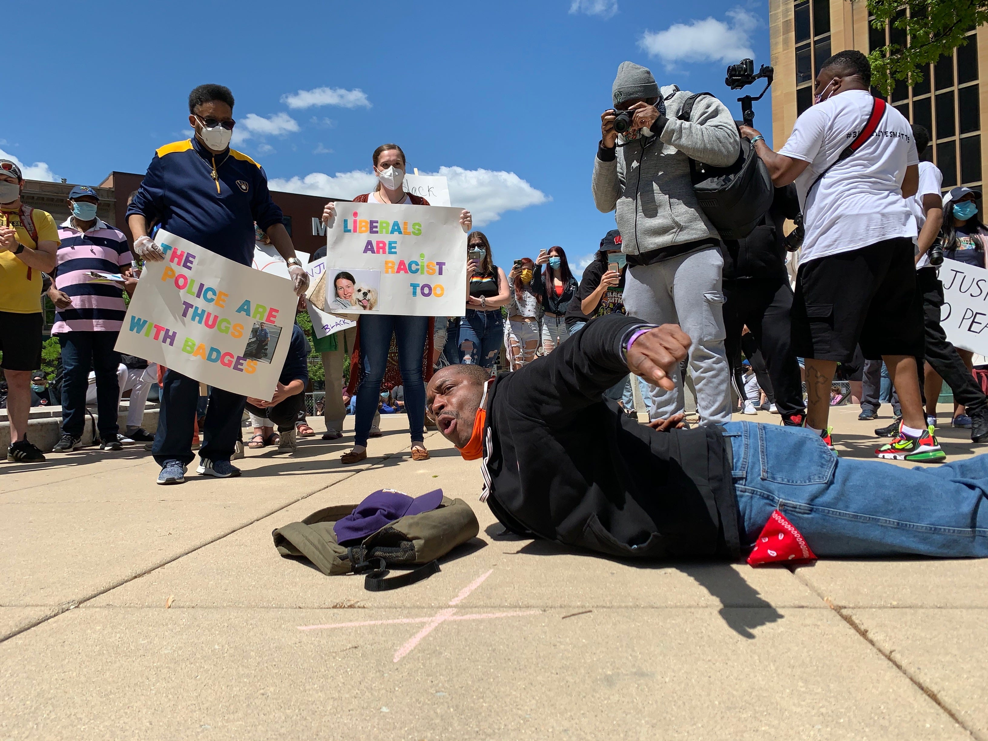 Robert Robinson, 43, lays on the sidewalk among protesters to show how George Floyd died during a protest in Madison on May 30, 2020.