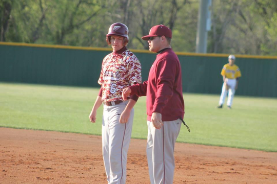 Chris Biggs (right) talks to a Riverdale player during a past Warrior game. Biggs was hired as head baseball coach at La Vergne for the 2021 season.