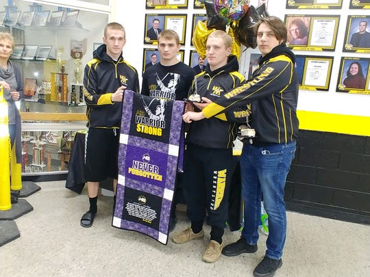 Watkins Memorial graduates Lucas Rummings, Cole Foor, C.J. Martin and Chrystian Warchyld hold a quilt last winter on senior night made to remember Mason Boyd, who was a teammate in 2018 when he died in a car crash. Foor and Martin are recipients of the Mason R. Boyd Wrestling Scholarship.