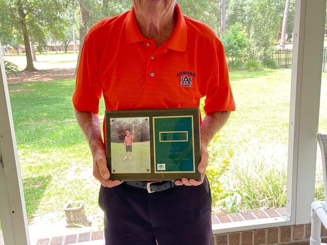 Huston Smith holds a plaque that recognizes his most-recent hole-in-one last January. Smith has shot 15 hole-in-ones and bowled two perfect games during his life.