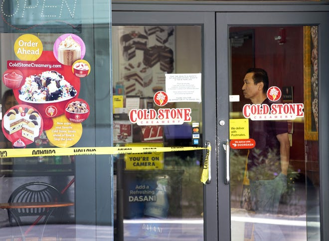 Chung Kang, owner of Cold Stone Creamery at the Arizona Center in Phoenix, watches crews board up his windows after they were shattered during a Black Lives Matter protest on May 29, 2020. The outraged was sparked after the death of George Floyd.
