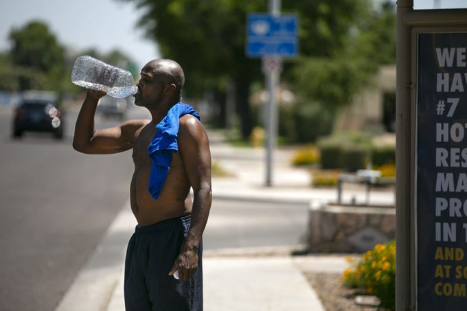 Kelly Wood waits for the bus along 44th Street in Phoenix, to take him home to his Phoenix apartment, on Friday afternoon, May 29, 2020. According to the National Weather Service, Phoenix reached 112 degrees at Sky Harbor International Airport, which tied a previous record high temperature for the date which was set in 1910.