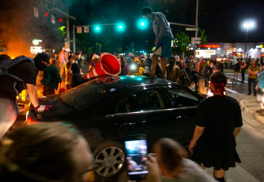 Protesters jump on a car that tried to drive through the blockage at 7th Ave. at Jefferson St. in Eugene May 30, 2020, during a protest over the killing of George Floyd in  Minneapolis, Minnesota.