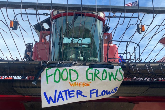 A sign is shown on the front of farm equipment near Merrill, Ore., Friday, May 29, 2020. Farmers upset about water issues planned a convoy in southwest Oregon.