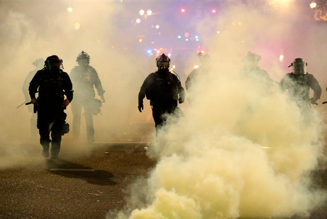Policemen walk enveloped by tear gas in Portland, Friday, March 29, 2020.  Afterhours of largely peaceful demonstrations,violence escalated downtown late in the evening.