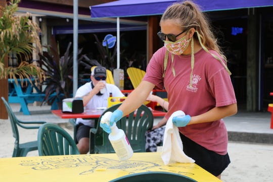 A Fish Tales staff member sanitizes a table at the restaurant after a group of patrons finished eating on May 29, 2020 in Ocean City.