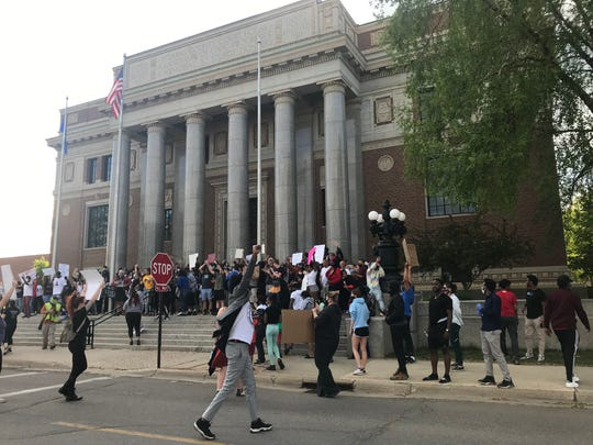 Protesters paused at the Stearns County Courthouse Friday night during a peaceful walk through downtown St. Cloud. The demonstration broke off from the flower drop off as it ended Friday night.