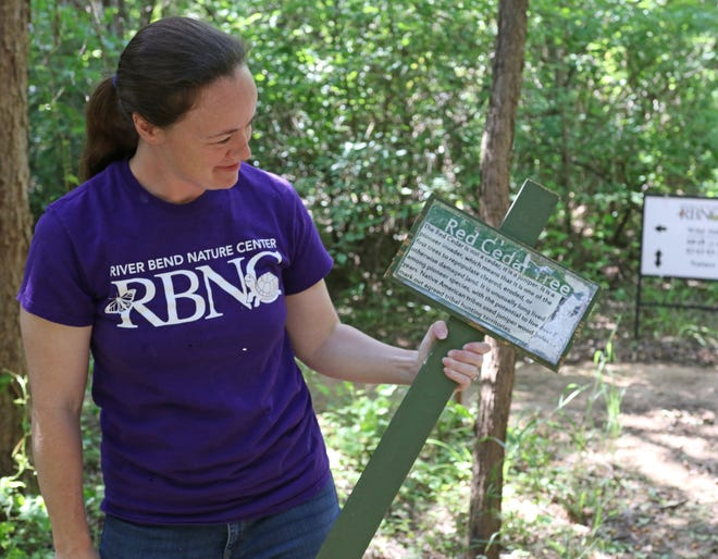 Jennica Lambert, exhibits curator, holds an old sign Friday, May 29, 2020, at the River Bend Nature Center.