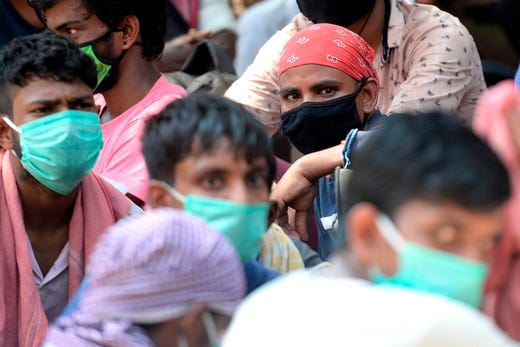 Stranded migrant labourers gather at an assembling centre to get transferred to a railway station to board on a special train to Bihar after the government eased a nationwide lockdown imposed as a preventive measure against the COVID-19 coronavirus, in Chennai on May 30, 2020.