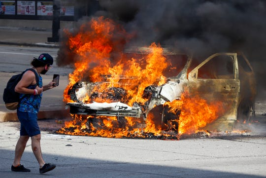 A Pittsburgh Police vehicle burns during a during a march in Pittsburgh, Saturday, May 30, 2020 to protest the death of George Floyd, who died after being restrained by Minneapolis police officers on Memorial Day, May 25. Saturday, May 30, 2020.