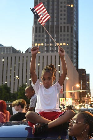 A child holds an American Flag as protestors march through the streets on May 29, 2020, in St Louis, Missouri.