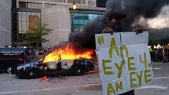 A police car burns during a protest in Atlanta, Friday, May 29.