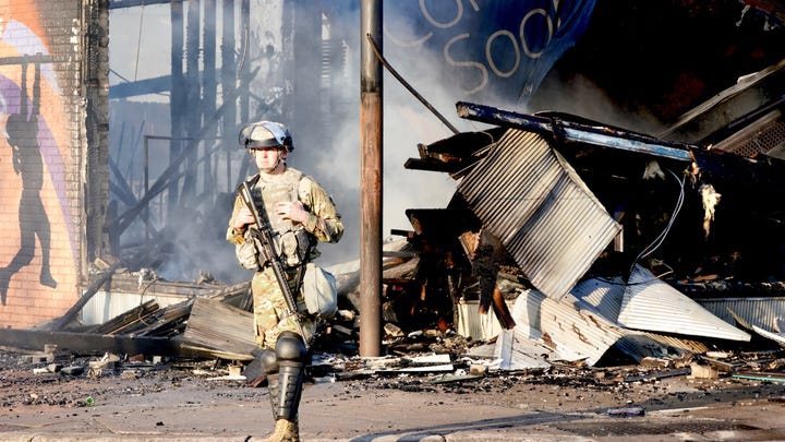 Members of the Minnesota National Guard controlled access to the streets on Lake Street near Columbus Avenue in Minneapolis. Humvees and trucks blocked the road as firefighters and public works officials tried to shut off leaking gas lines and clear rubble from the road. Saturday, May 30, 2020