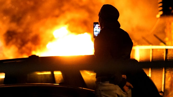 Several cars burn near a gas station during a night of rioting in Minneapolis over the of George Floyd.