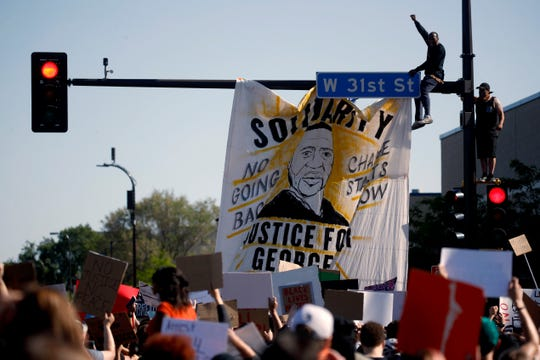 People react during a rally Saturday in Minneapolis. Protests continued following the death of George Floyd.