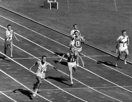 Bobby Joe Morrow, bottom left, of the United States, crosses the finish line to give the U.S. team the gold medal for the 400-meter relay at the Summer Olympic Games on Dec. 1, 1956, in the Olympic Stadium in Melbourne, Australia. Morrow, the Texas sprinter who won three gold medals in the 1956 Melbourne Olympics while a student at Abilene Christian University, died Saturday, May 30, 2020. He was 84. (AP Photo/Pool, File)
