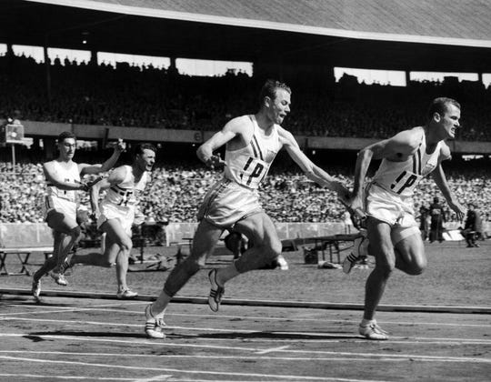Thane Baker, of the United States, hands the baton to Bobby Joe Morrow for the last exchange in the first heat of the first round of the 400-meter relay at Summer Olympic Games relay event on Nov. 30, 1956, in Melbourne, Australia. Morrow, the Texas sprinter who won three gold medals in the 1956 Melbourne Olympics while a student at Abilene Christian University, died Saturday, May 30, 2020. He was 84. (AP Photo/Pool, File)