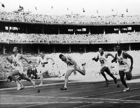 The United States' Bobby Joe Morrow (55) crosses the finish line of the men's 100-meter race in 10.5 seconds, equaling an Olympic record, during the Summer Olympics on Nov. 23, 1956, in Melbourne, Australia. Morrow, the Texas sprinter who won three gold medals in the 1956 Melbourne Olympics while a student at Abilene Christian University, died Saturday, May 30, 2020. He was 84. (AP Photo/File)