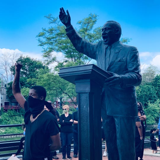 Talon Thomas stands in front of the Martin Luther King Jr. statue in Binghamton, fist raised, after singing a song to remember victims of police brutality.