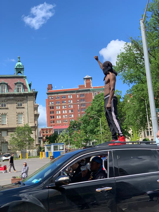 Talon Thomas, 27, Binghamton, raises a fist while atop a vehicle during the peaceful march through the city May 31, 2020.