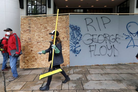 A woman helping to clean up downtown walks near graffiti Sunday in Seattle, following a night of unrest and protests over the death of George Floyd, a black man who was in police custody in Minneapolis.
