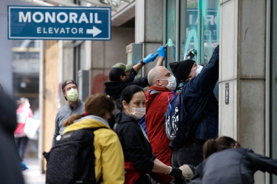 Volunteers crowd together as they clean graffiti off of windows on Sunday, May 31, 2020, in downtown Seattle, following protests the night before over the death of George Floyd, a black man who was in police custody in Minneapolis. On Sunday morning, hundreds of people of all ages turned out in downtown Seattle to help clean up the damage, sweeping up broken glass and cleaning off graffiti.