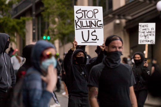 Demonstrators march at 5th Avenue and Marion Street in downtown Seattle to show solidarity with Minneapolis and protesting police brutality on Friday, May 29, 2020. George Floyd died earlier this week in police custody in Minneapolis. ( (Amanda Snyder /The Seattle Times via AP)