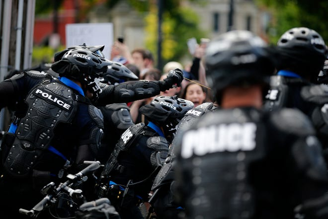 A Cincinnati Police officer deploys pepper spray into the crowd as protesters and police clash at the intersection of 12th and Race Streets near Washington Park in the Over-the-Rhine neighborhood of Cincinnati on Saturday, May 30, 2020. Hundreds of demonstrators took to the streets of Over-the-Rhine and downtown in solidarity with protesters in other US cities, speaking out against police brutality.