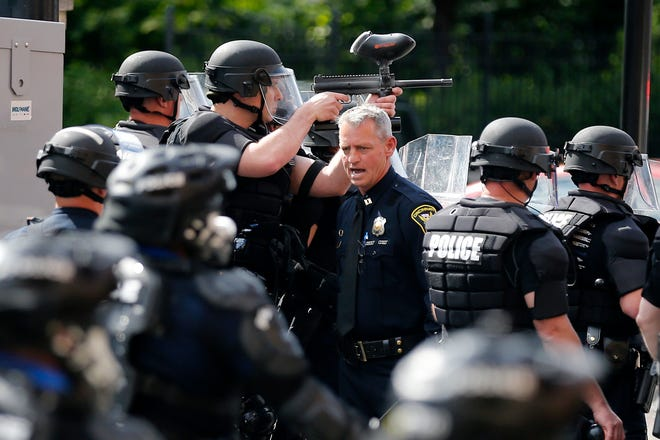 Police in riot gear fire paintball guns loaded with pepper balls and flashing grenades as protesters and police clash at the intersection of 12th and Race Streets near Washington Park in the Over-the-Rhine neighborhood of Cincinnati on Saturday, May 30, 2020. Hundreds of demonstrators took to the streets of Over-the-Rhine and downtown in solidarity with protesters in other US cities, speaking out against police brutality.