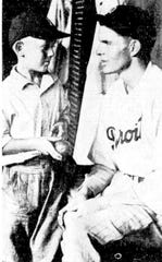 Nine-year-old Don Hubert, left, consoles Detroit Tigers pitcher Tommy Bridges after Bridges lost a perfect game on the 27th batter on Aug. 5, 1932.