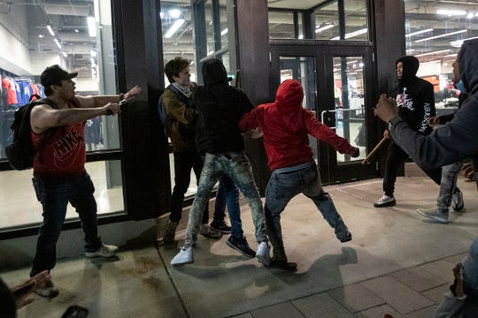 A group of protesters try to break into the Nike store on Woodward Avenue in Detroit as another group tries to stop them, Saturday, May 30, 2020.
