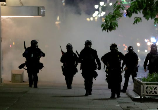 Detroit police officers walk through tear gas towards protesters Saturday, May 30, 2020 in Detroit Michigan.
