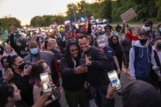 "Johnie Franklin of Flint Township, Mich., takes a selfie with Genesee County Sheriff Chris Swanson on May 30. Protesters at the Police Department were met by police in riot gear. Swanson asked one of the protesters what he wanted. The protester asked Swanson to walk with them, so he and some of his deputies did.  ""We're on the community's side,"" Swanson says. ""All we had to do was talk to them, and now we're walking with them. Everybody wins."""