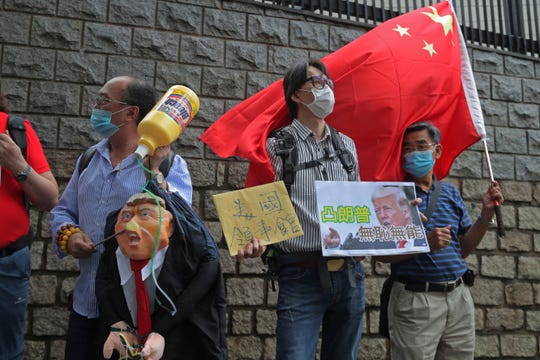 Pro-China supporters hold the effigy of U.S. President Donald Trump and Chinese national flag outside the U.S. Consulate during a protest, in Hong Kong, Saturday.