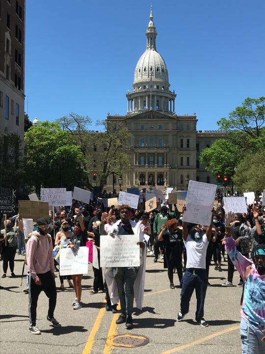 Hundreds of protesters march against police brutality near the Michigan Capitol on Sunday, May 31, 2020.