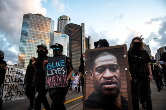 Protesters march toward the freeway while holding a photo of George Floyd during the second straight day to demonstrate against the alleged killing of George Floyd by Minneapolis police in Detroit on Saturday, May 30, 2020.