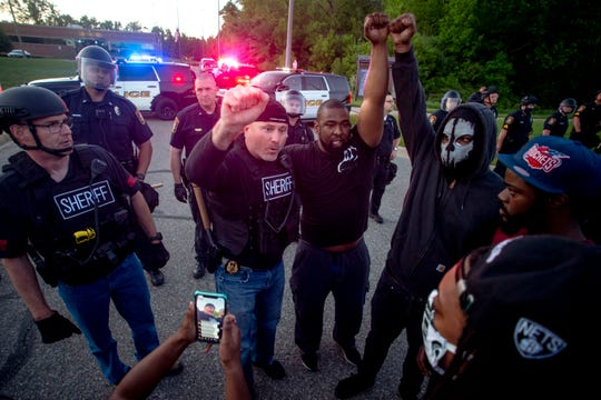 A Genesee County sheriff's deputy raises his fist in solidarity alongside protesters on Saturday, May 30, 2020, on Miller Road in Flint Township.