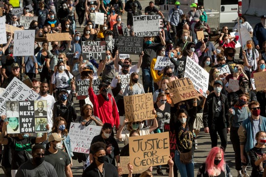 People march down Randolph Street in downtown Detroit on Sunday to protest against police brutality.
