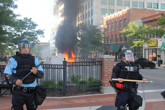 A car fire burns in  downtown Lansing after law enforcement officers moved protesters away from the vehicle. Protesters flipped the car after feuding with its driver, who had been escorted away earlier.