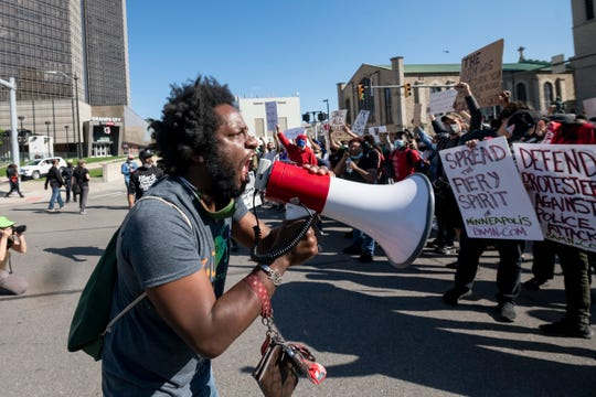 Organizer Tristan Taylor chants with the crowd while marching on Jefferson Ave in downtown Detroit May 31, 2020 to protest the death of George Floyd.