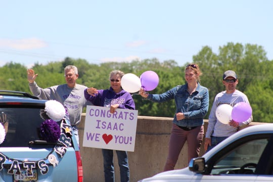 Residents on the State Street bridge wave at cars filled with Fremont Ross High School 2020 graduates and their families.