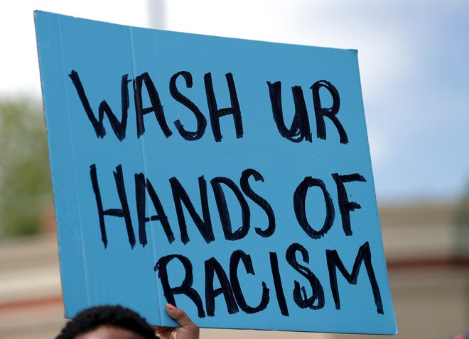 A sign reads 'Wash ur hands of racism' in response to the death of George Floyd on Sunday, May 31, 2020, in Green Bay, Wis. Floyd died after being restrained by Minneapolis police officers on Memorial Day.