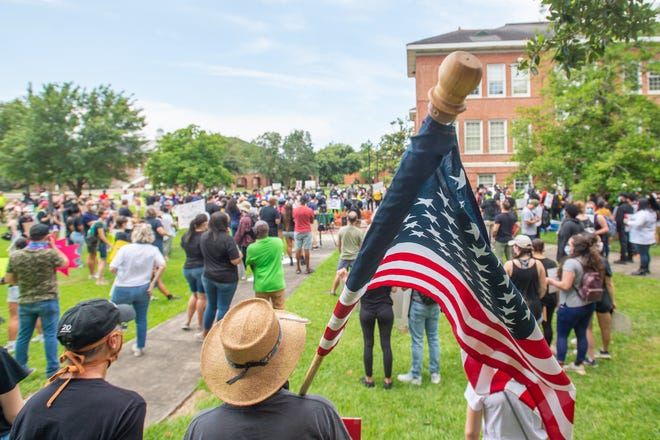 Protesters rally in solidarity with those in Minnesota over the killing of George Floyd by police in Lafayette, LA. Sunday, May 31, 2020.