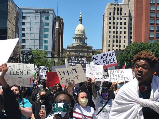 Protesters march down Michigan Avenue from the Capitol in Lansing Sunday, May 31, 2020.