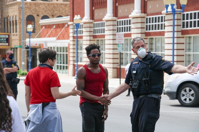 """Marion Police Major Jay Mcdonald talks to Brandon Rosvanis in Marion on May 30, 2020. Rovanis, a protestor with the Black Lives Matter movement, says he's been to several of the protests around the state, including Columbus. He credited the peacefulness of the protests to the people of Marion and the Marion Police Department. """"They came here for support, they are very vocal,"""" Rosvanis said about the protestors. """"They would rather speak with their words, rather than violence."""""""