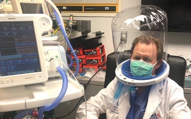 """Patrick Herlihy, chief of critical care at Baylor St. Luke's in Houston wearing a device that helps patients get more oxygen. It's known as """"the Helmet""""."""