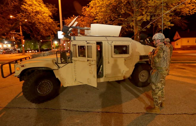 A Member of the Wisconsin National Guard is seen near an armored vehicle at the Milwaukee Public Library parking lot near Milwaukee Police District 5 police station in Milwaukee on Saturday, May 30, 2020. Protests continued in response to the the death of George Floyd and other instances of police brutality.
