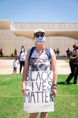 A protester holds a sign as the Monroe/Ouachita Parish Branch of the NAACP held a second protest against racial injustice, police brutality and systemic oppression at the Monroe Civic Center on Sunday.