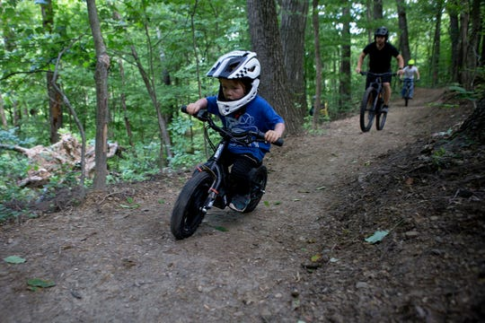 Tetton Pellett, 4, who has been riding his mountain bike since he was 3, tests out a new trail at Horns Hills Park on Saturday morning with his dad, Tommy Pellett. Through the Horns Hill Park Improvement Fund, the goal is to have nine trails by the end of an ongoing project.