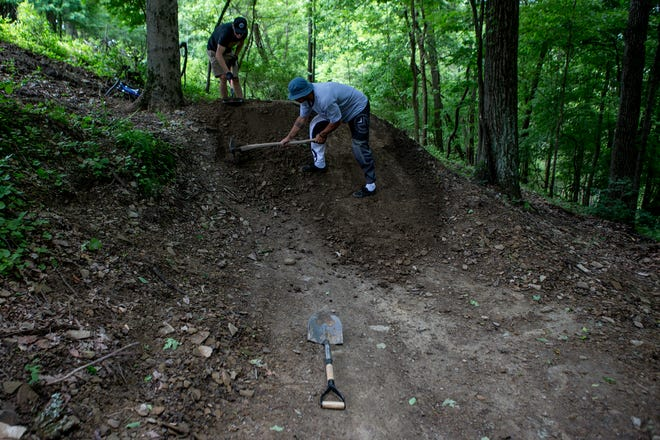 Cameron Reagan and Grant Shumaker fix a jump on one of the mountain bike trails at Horns Hills Park on Saturday morning. Through the Horns Hill Park Improvement Fund, the goal is to have nine trails by the end of an ongoing project.